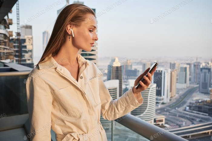 Beautiful girl with wireless earphones using cellphone on balcony with city view