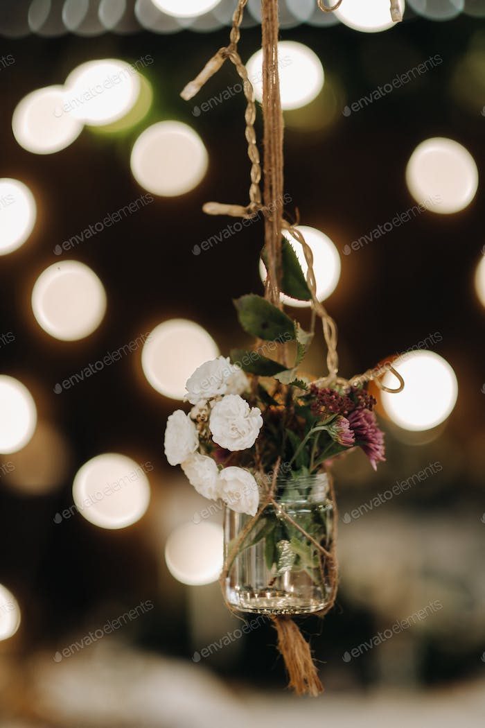 the wedding decor hangs near the candlelit dinner table.Dinner with candles