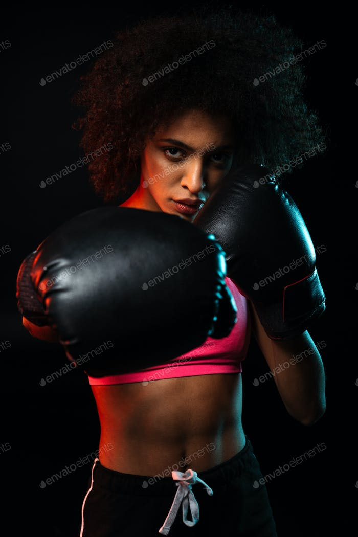 Image of african american sportswoman working out in boxing gloves