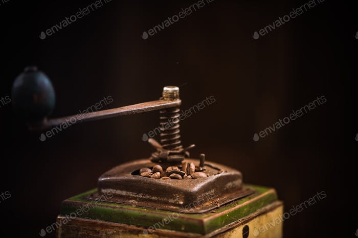 Toned image of vintage coffee grinder with roasted beans