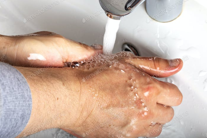 Man washing soapy hands in bathroom