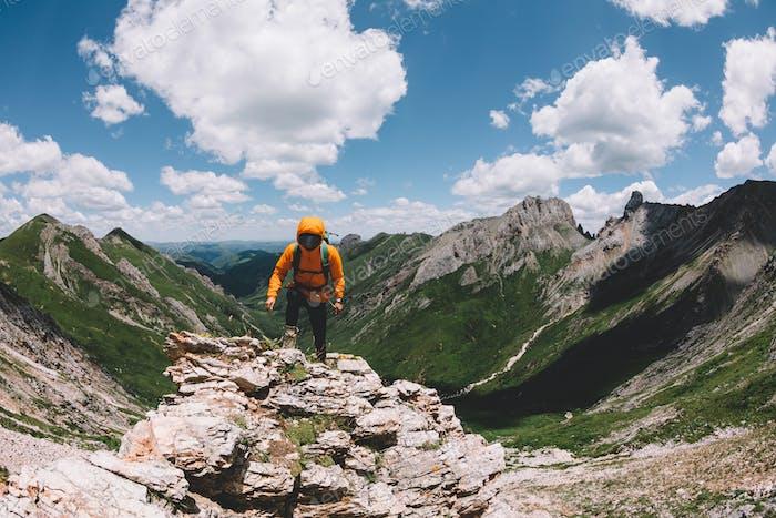 Successful woman backpacker hiking on sunset alpine mountain peak