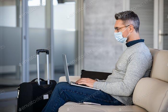 Hombre de negocios maduro usando máscara durante el viaje y el uso de la computadora portátil