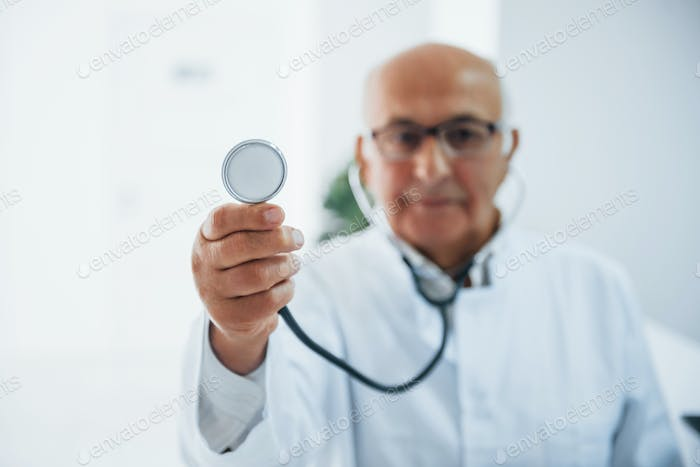 Portrait of senior doctor with stethoscope and in white uniform that stands in the clinic