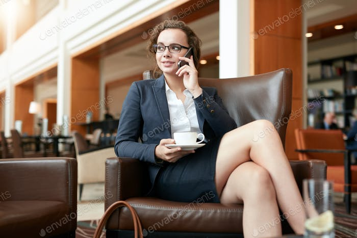 Businesswoman sitting in cafe talking on mobile phone