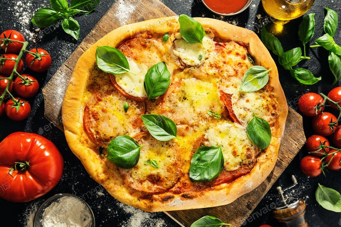 Homemade pizza with mozzarella on dark background
