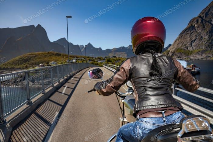 Biker girl rides on road in Norway.