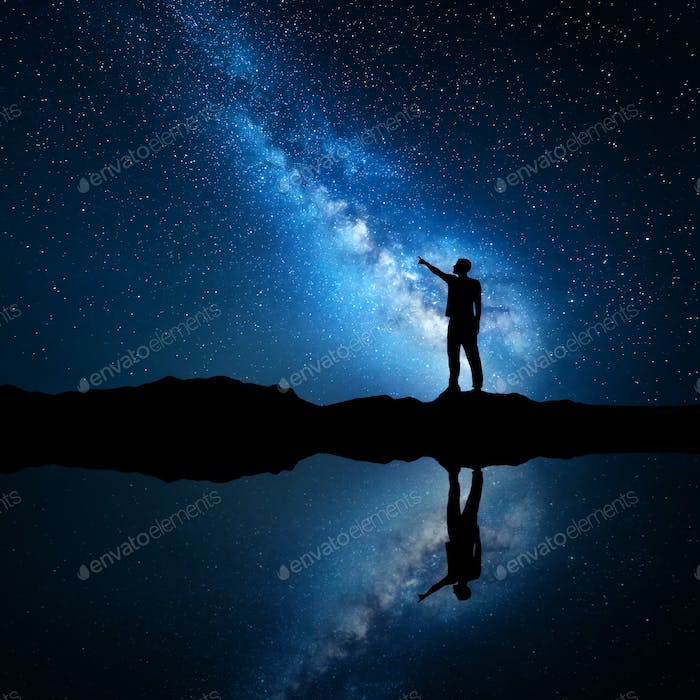 Milky Way. Silhouette of a standing man near the lake