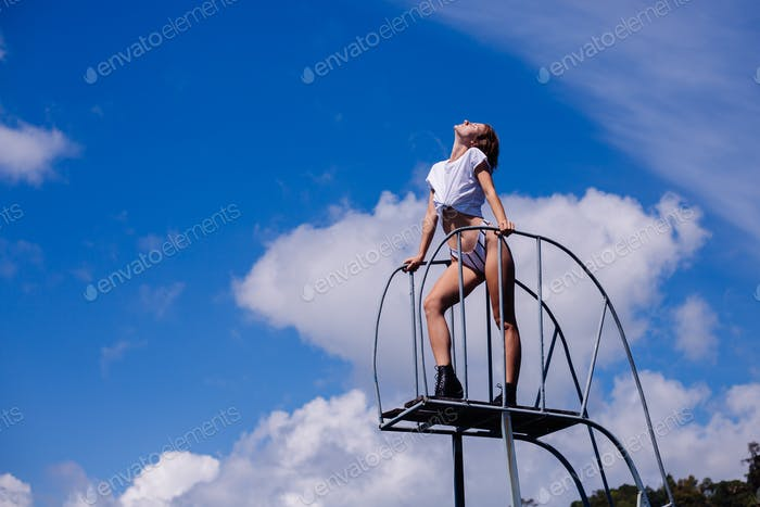 Woman in white shirt and panties on stairs to sky, clouds and blue sky on background
