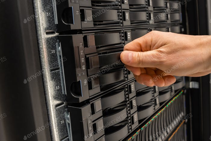 Male IT Engineer Replacing Server Drive in SAN At Datacenter