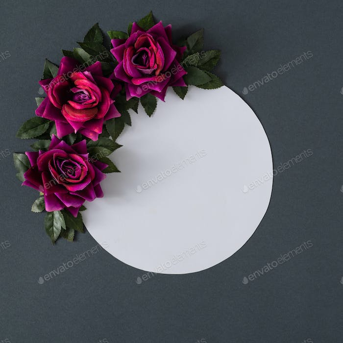 Purple flowers and leaves on gray background. Spring season minimal concept. Women's day