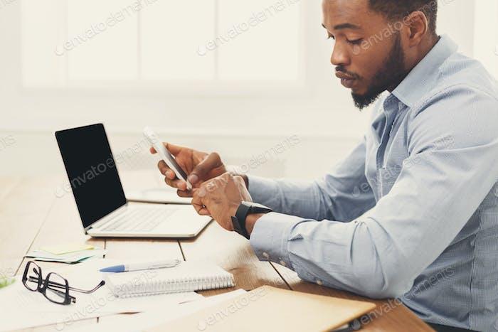 Junge schwarze Geschäftsmann mit Smartwatch im Büro