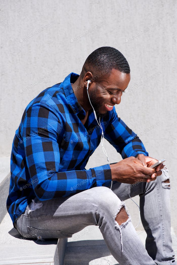 handsome man smiling with headphones and smart phone