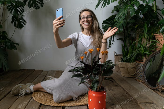 Happy woman gardener smiling talking on video call on cellphone, say hello, sitting in home garden