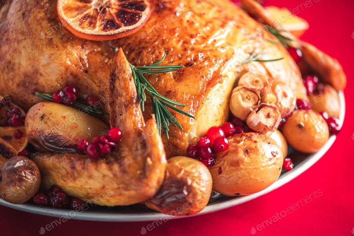 Whole roasted chicken with oranges, cranberries, spices and herbs. Copy space. Friends or family