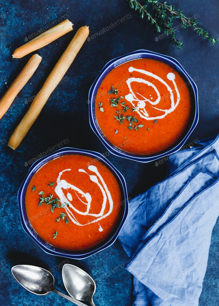 Top view of two portions of red tomato cream soup