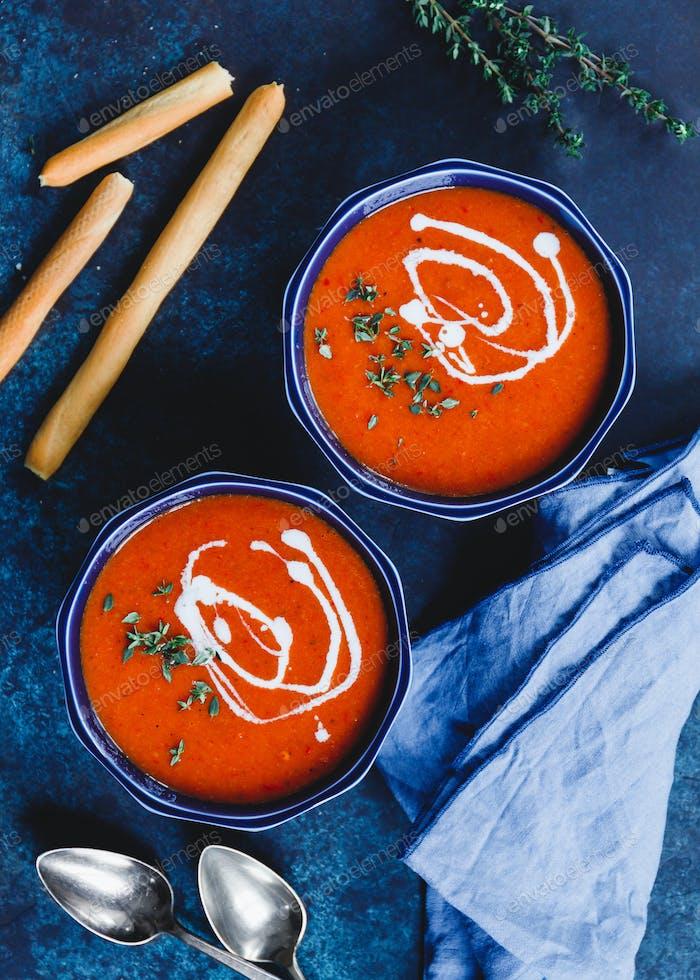 Draufsicht von zwei Portionen rote Tomaten-Sahnesuppe