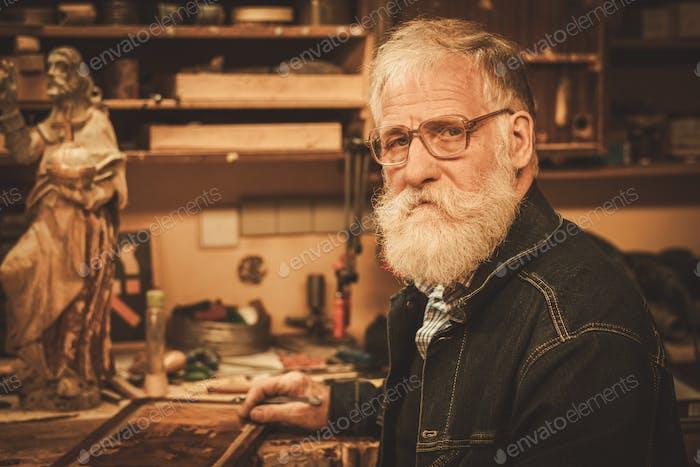 Portrait of senior restorer in his workshop