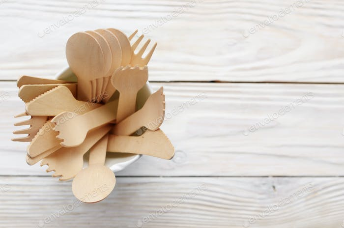 Wooden single use kitchenware in paper cup on white table. Top v