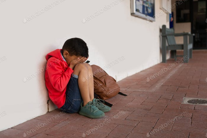 Sad schoolboy sitting alone with hands covering his face on floor in corridor