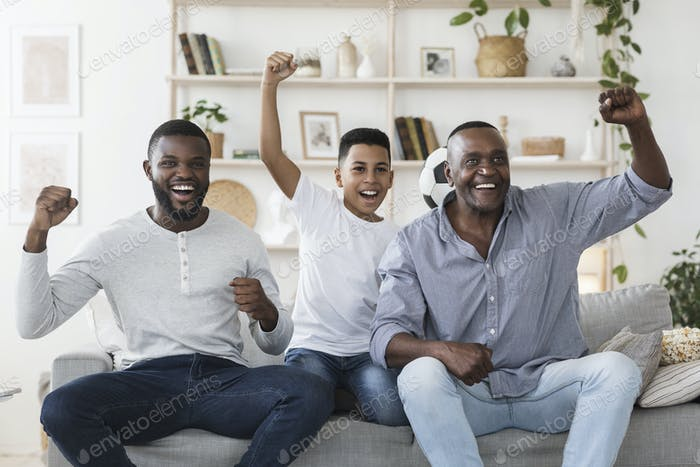 Joyful Father, Son And Grandfather Watching Soccer On TV And Cheering