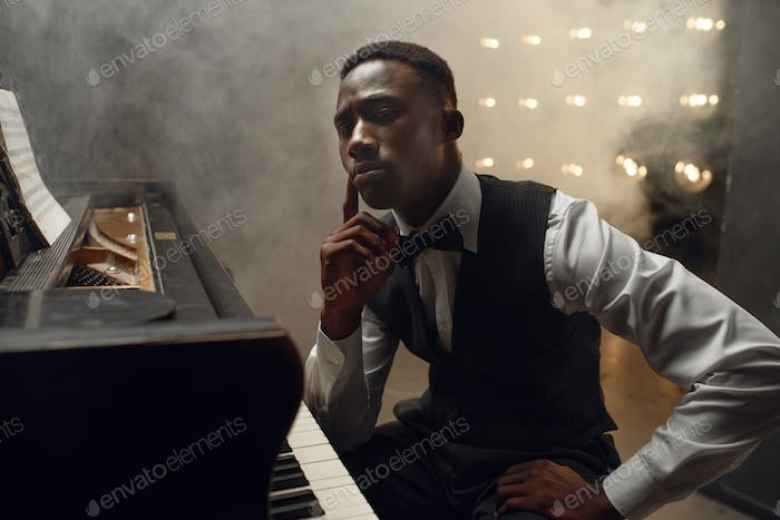 Black grand piano musician poses on the stage
