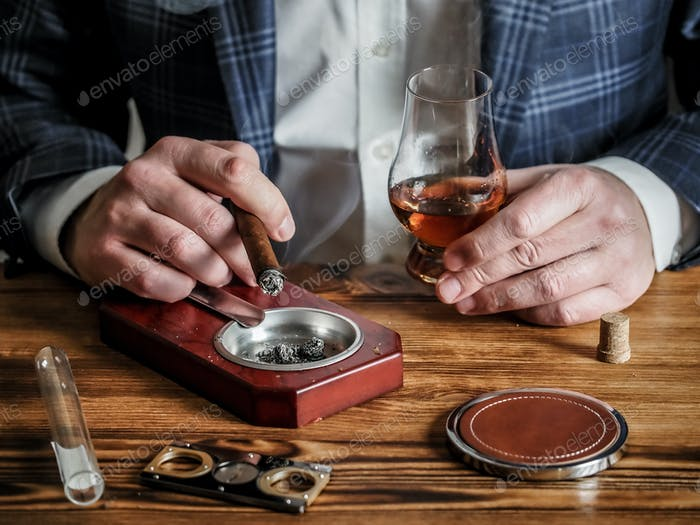 Man at a bar drinks whisky and smokes a cigar