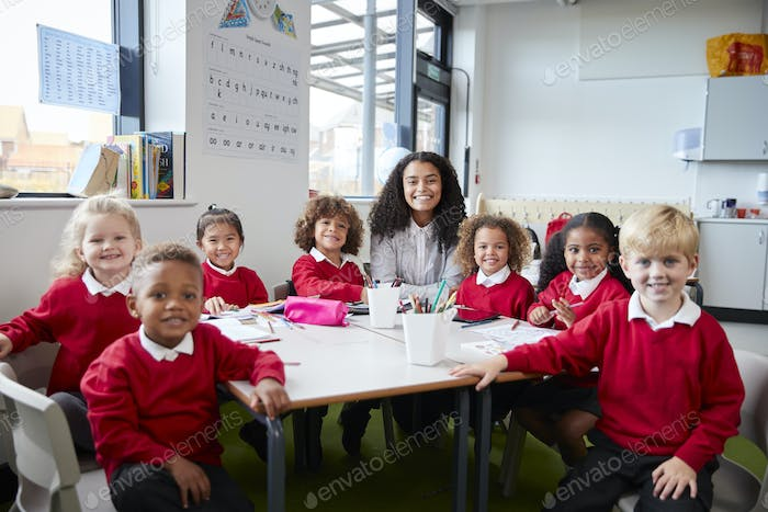 Portrait of infant school teacher and kids sitting at table in a classroom looking to camera smiling