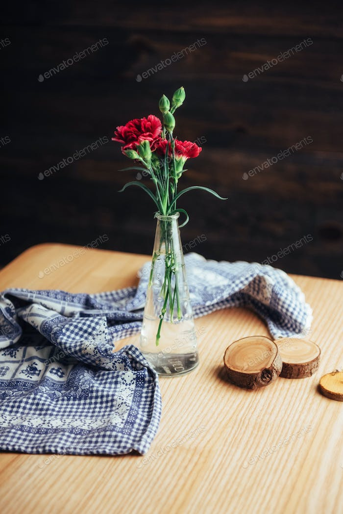 delicate bouquet of carnations in a vase on wooden table