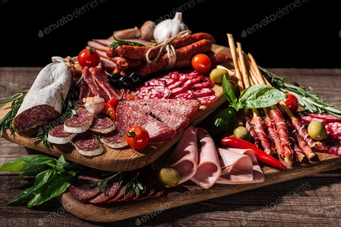 cutting boards with delicious salami, smoked sausages, ham and vegetables on wooden rustic table