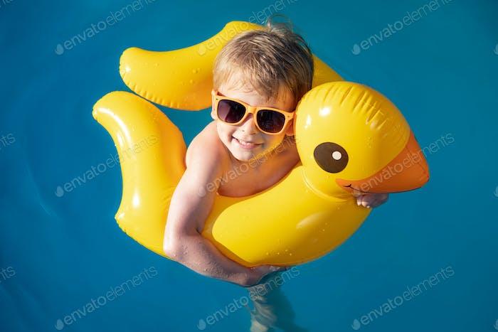 Glückliches Kind schwimmt in den Sommerferien