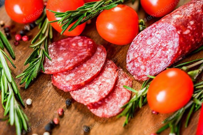 Leckere Salami mit Tomaten und Pfefferkorn schließen