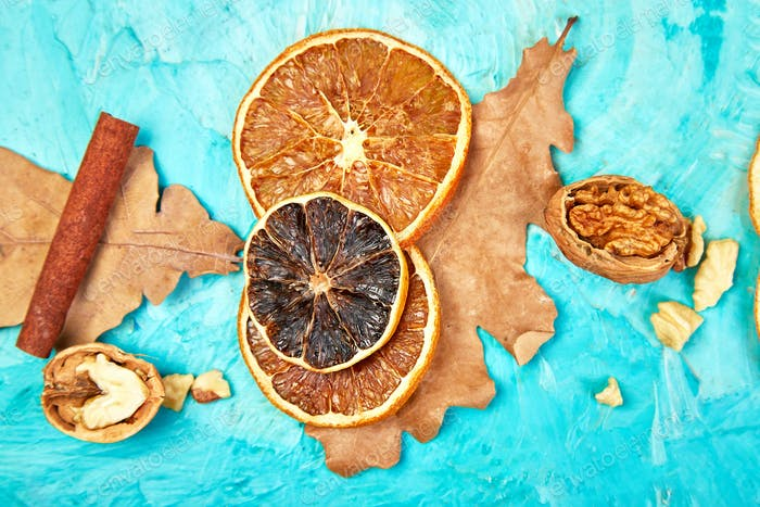 Autumn composition background with slices of dried oranges, leaves and cinnamon.