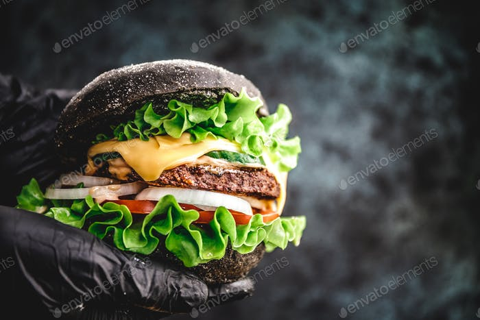 Hands in black gloves hold a big black burger with marble beef patty, cheese and fresh vegetables