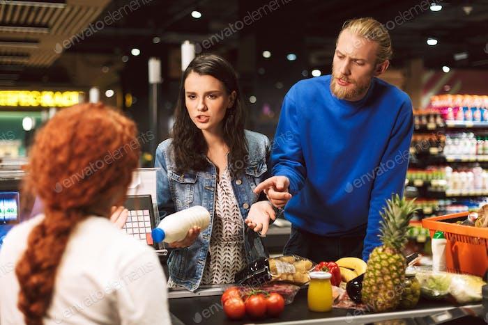 Junge Frau mit Milch der Flasche in der Hand und Mann emotional sprechen