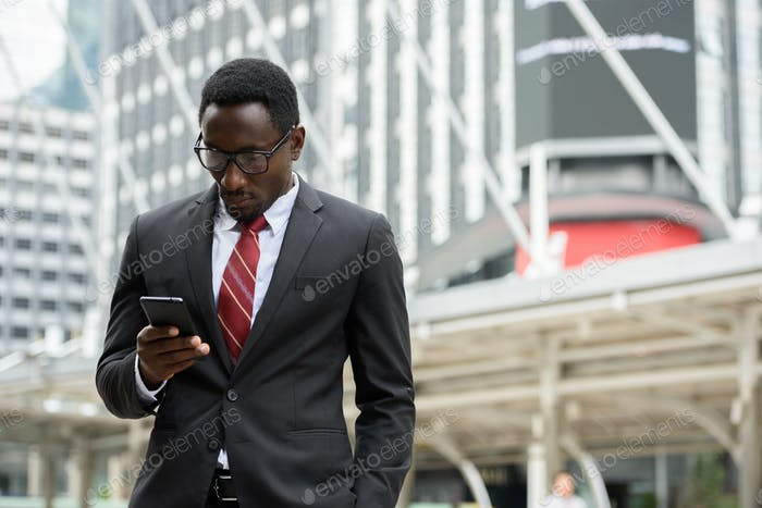 Young handsome African businessman using mobile phone in front of modern building at Bangkok city