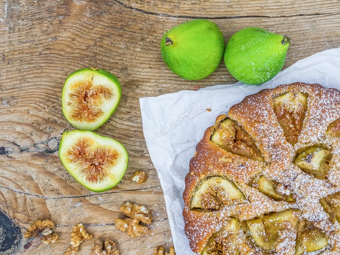 Fig pie with fresh figs and walnuts over a wood background