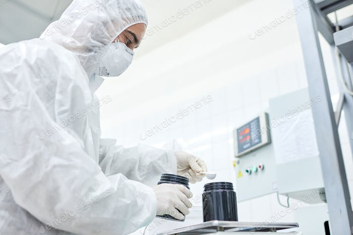 Factory worker adding product to plastic container