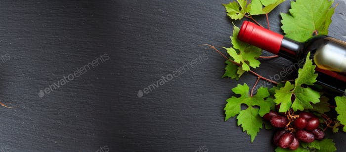Red wine bottle and fresh grapes on black background