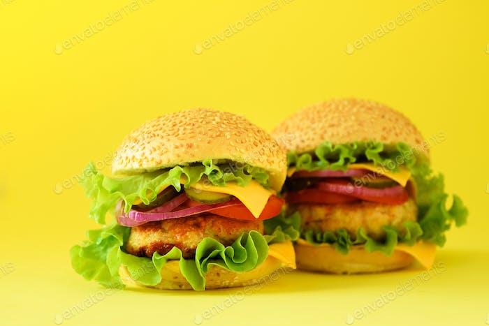 Fast Food - saftiger Hamburger, Pommes Frites Kartoffeln und Cola-Drink auf gelbem Hintergrund. Mitnehmen