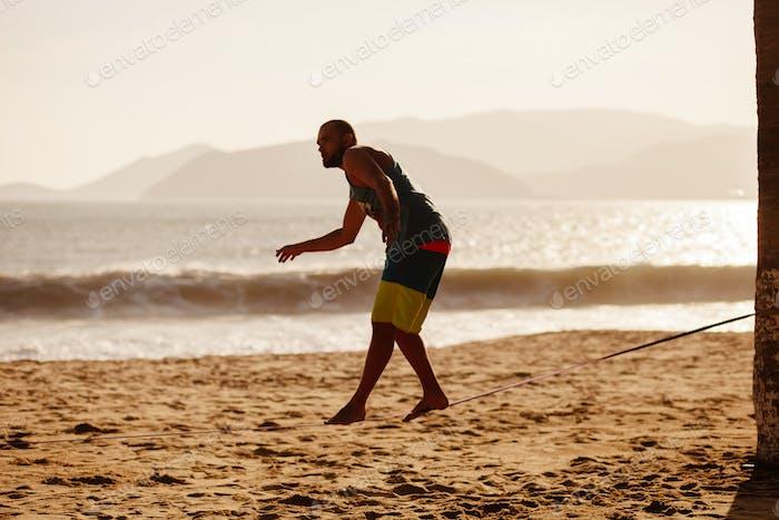 teenage balancing on slackline with sea view