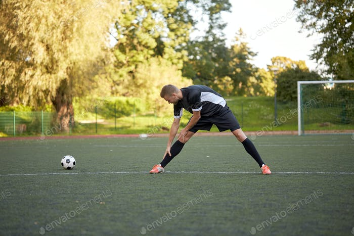 soccer player stretching leg on field football
