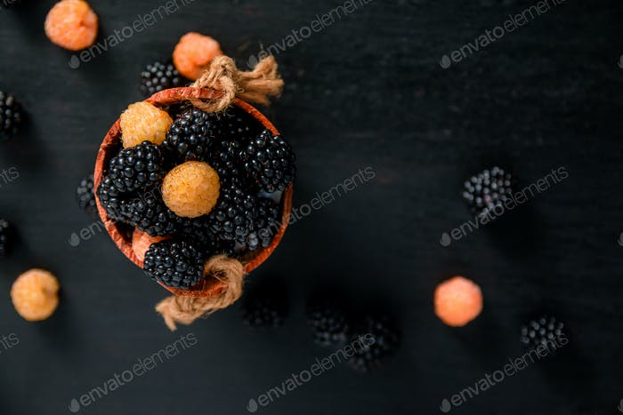 Black and yellow raspberries in a wooden basket on   background. Frame. Copy space. Top view.