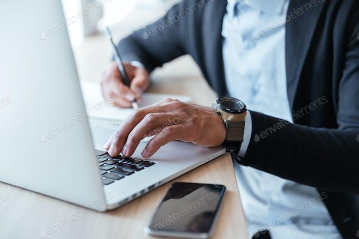 Close-up portrait of multitasking mans hands using laptop