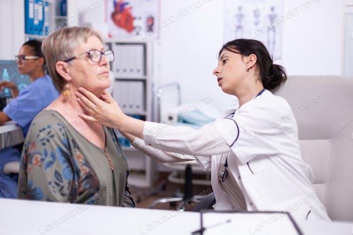 Joven médico palpante cuello de mujer mayor