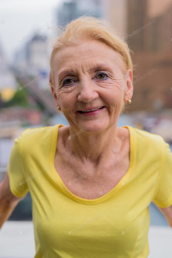 Beautiful senior woman smiling outdoors in city