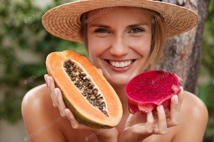 Close up shot of beautiful smiling female with appealing appearance, pleasant smile, holds papaya an