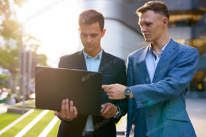 Two young handsome businessmen working together outside the buil