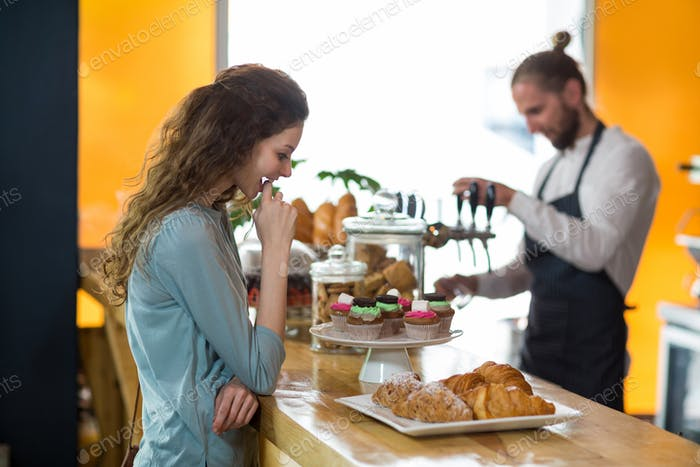 Smiling woman looking at croissant