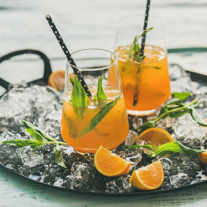 Refreshing cold alcoholic summer cocktail with orange and peppermint